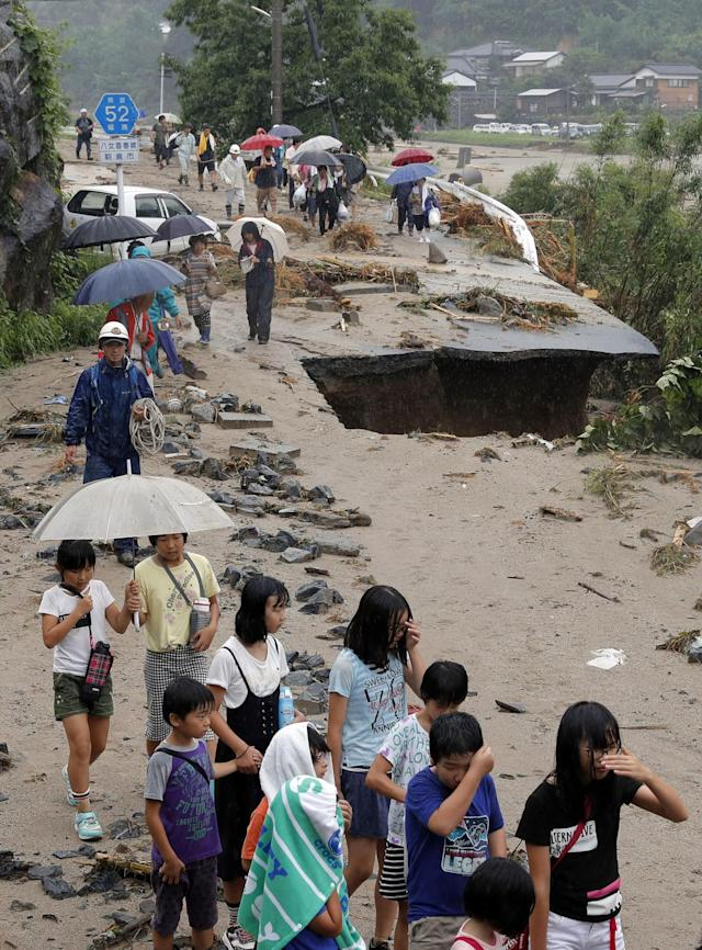 <p>People walk through a damaged road to flee from an isolated school in Asakura, Fukuoka prefecture, southwestern Japan Thursday, July 6, 2017. Troops were working Thursday to rescue families left stranded by flooding in southern Japan. Heavy rain warnings were in effect for much of the southern island of Kyushu after Typhoon Nanmadol swept across Japan earlier in the week. (Photo: Takuto Kaneko/Kyodo News via AP) </p>