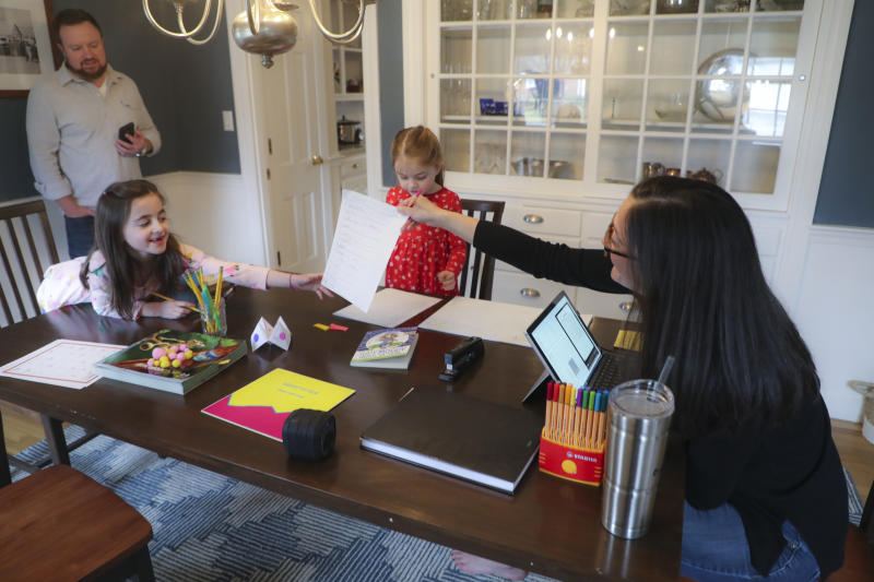 Sarah Yunits checks her daugher Ada's homework while Cora waits her turn as dad Conor Yunits is on a work conference call at their home in Brockton on March 19, 2020. (Photo by Matthew J. Lee/The Boston Globe via Getty Images)