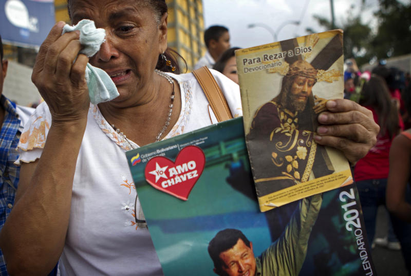"FILE - In this Feb. 24, 2012 file photo, a supporter of Venezuela's President Hugo Chavez cries as she holds a picture of him, as well as a poster of Jesus, during his caravan to the airport to travel to Cuba for surgery to remove a tumor, in Caracas, Venezuela. The poster reads in Spanish ""I love Chavez."" Chavez has spent much of his career praising the socialist ideas of famed atheists such as Karl Marx and Fidel Castro. However, now in the thick of a prolonged battle against cancer, Chavez is drawing inspiration more than ever from Jesus Christ. (AP Photo/Ariana Cubillos, File)"