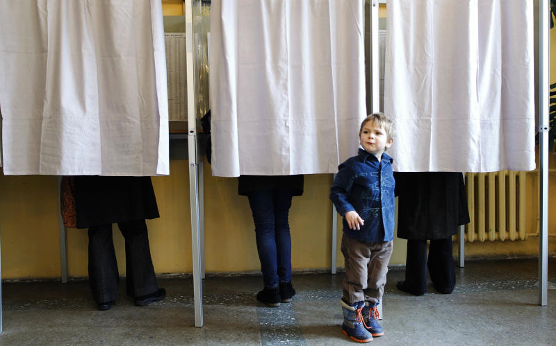 A child looks on while standing in a polling station in Vilnius, Lithuania, Sunday, Oct. 14, 2012. Lithuanians are expected to deal a double-blow to the incumbent conservative government in national elections Sunday by handing a victory to opposition leftists and populists and saying no to a new nuclear power plant that supporters claim would boost the country's energy independence (AP Photo/Mindaugas Kulbis)