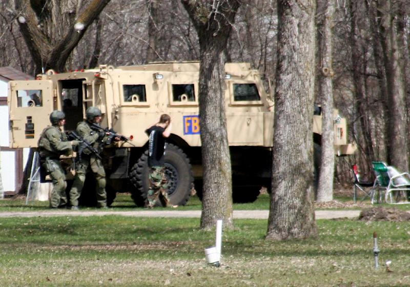 """FILE - This May 3, 2013, photo provided by Jeremy Jones shows authorities with Buford Rogers, right, who belongs to a tiny local militia, during a raid on a mobile home in Montevideo, Minn. Rogers, 25, is scheduled to be sentenced Monday, April 28, 2011 after pleading guilty to one count of possessing a firearm illegally and one count of possessing an unregistered destructive device, namely """"two black powder and nail devices,"""" which he admitted he made himself. Prosecutors are seeking more than five years in prison, arguing that Rogers poses a threat to public safety, noting the items were designed solely to injure people. (AP Photo/Montevideo American-News, Jeremy Jones, File) MANDATORY CREDIT"""