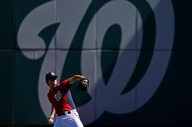WASHINGTON, DC - SEPTEMBER 17: Pitcher Erik Davis #51 of the Washington Nationals wears a Navy hat as he warms up before playing the Atlanta Braves at Nationals Park on September 17, 2013 in Washington, DC. Yesterday 13 people were shot and killed by a gunman, including the shooter, at the Navy Yard in Washington, DC. (Photo by Patrick Smith/Getty Images)