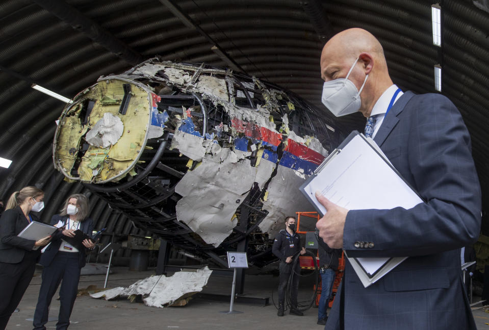 FILE- In this Wednesday, May 26, 2021, file photo Presiding judge Hendrik Steenhuis, right, and other trial judges and lawyers view the reconstructed wreckage of Malaysia Airlines Flight MH17, at the Gilze-Rijen military airbase, southern Netherlands. The trial in absentia in a Dutch courtroom of three Russians and a Ukrainian charged in the downing of Malaysia Airlines flight MH17 in 2014 moves to the merits phase, when judges and lawyers begin assessing evidence. (AP Photo/Peter Dejong, File)
