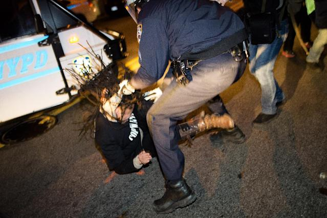 "A demonstrator is thrown to the ground by her hair during a march following a vigil held for Kimani ""Kiki"" Gray in the East Flatbush neighborhood of New York's Brooklyn borough, Wednesday, March 13, 2013, in New York. According to the NYPD, the teen pointed a .38-caliber revolver at the plainclothes officers, who responded by shooting him to death. (AP Photo/John Minchillo)"