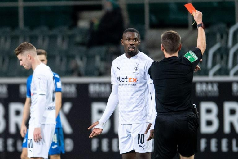 Moenchengladbach forward Marcus Thuram is shown a red card for spitting at an opponent on Saturday
