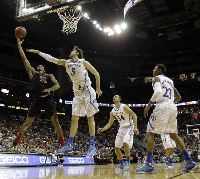 Texas Tech forward Jordan Tolbert (32) puts up a shot under pressure from Kansas center Jeff Withey (5) during the first half an NCAA college basketball game in the Big 12 men's tournament Thursday, March 14, 2013, in Kansas City, Mo. (AP Photo/Charlie Riedel)