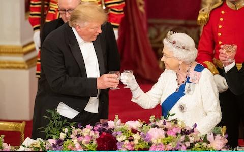 Donald Trump and the Queen make a toast at Buckingham Palace in June - Credit: Getty