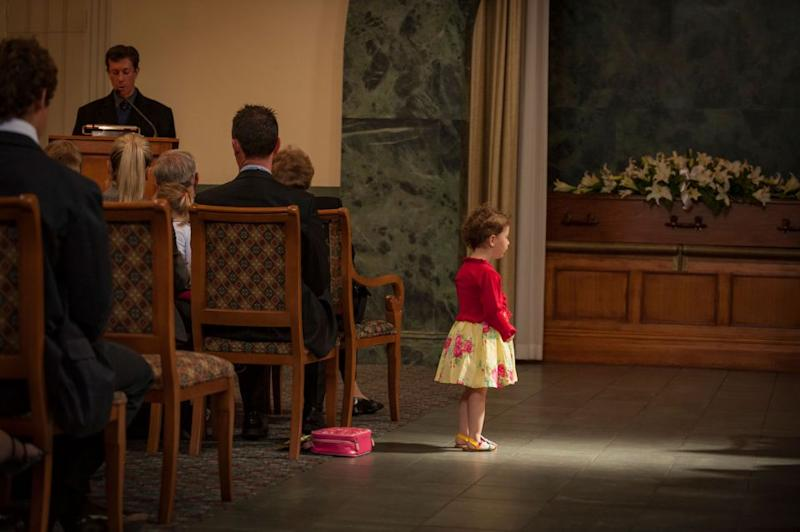 A little girl is caught in a ray of light at a funeral. Source: Supplied/John Slaytor.