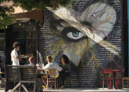 People eat outdoors outdoors at a soul food restaurant in Los Angeles on Saturday, Jun. 5, 2021. Most of California's coronavirus restrictions on businesses and public gatherings will end June 15. (AP Photo/Damian Dovarganes)
