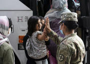 FILE - In this Monday, Aug. 30, 2021, file photo, Army Pfc. Kimberly Hernandez gives a high-five to a girl evacuated from Kabul, Afghanistan, before boarding a bus after they arrived at Washington Dulles International Airport, in Chantilly, Va. U.S. religious groups of many faiths are gearing up to assist the thousands of incoming refugees. (AP Photo/Jose Luis Magana, File)