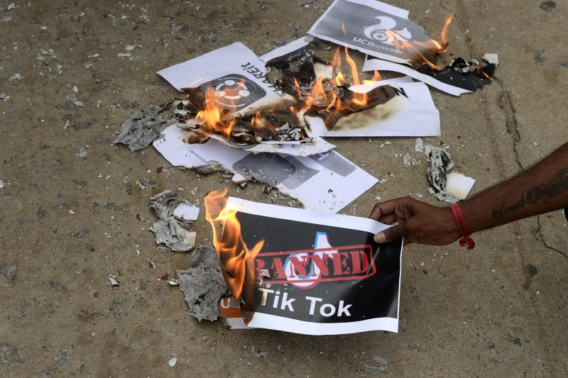 """Members of the City Youth Organisation burn posters with the logo of the Chinese owned video-sharing 'Tik Tok' app in support of the Indian government for banning the wildly popular app, in Hyderabad on June 30, 2020. - TikTok on June 30 denied sharing information on Indian users with the Chinese government, after New Delhi banned the wildly popular app citing national security and privacy concerns. """"TikTok continues to comply with all data privacy and security requirements under Indian law and have not shared any information of our users in India with any foreign government, including the Chinese Government,"""" said the company, which is owned by China's ByteDance. (Photo by NOAH SEELAM / AFP) (Photo by NOAH SEELAM/AFP via Getty Images)"""