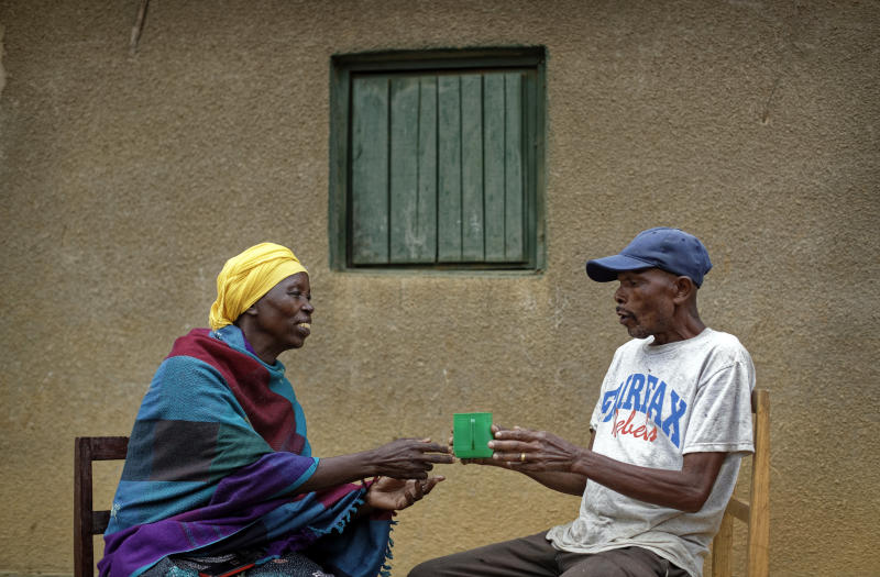 """In this photo taken Thursday, April 4, 2019, genocide survivor Laurencia Mukalemera, left, a Tutsi, is offered a cup of water by Tasian Nkundiye, right, a Hutu who murdered her husband and spent eight years in prison for the killing and other crimes, before being interviewed at Nkundiye's home in the reconciliation village of Mbyo, near Nyamata, in Rwanda. Twenty-five years after the genocide the country has six """"reconciliation villages"""" where convicted perpetrators who have been released from prison after publicly apologizing for their crimes live side by side with genocide survivors who have professed forgiveness. (AP Photo/Ben Curtis)"""