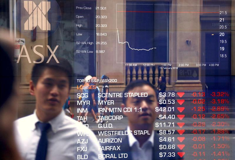 Pedestrians are reflected in a window displaying stock prices at the Australian Securities Exchange in Sydney