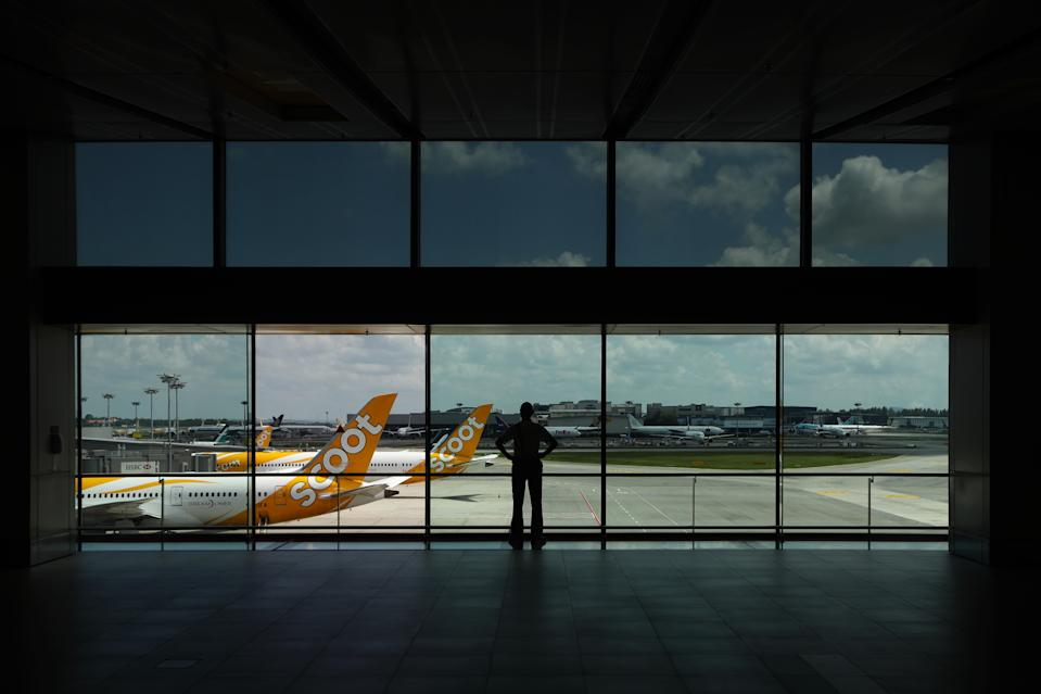 SINGAPORE - MARCH 24:  A man looks at Scoot aircrafts sitting on the tarmac at Changi Airport on March 24, 2020 in Singapore. Singapore Airlines will cut its capacity by 96% till the end of April as border restrictions tighten worldwide due to the spread COVID-19 pandemic.  (Photo by Suhaimi Abdullah/Getty Images)