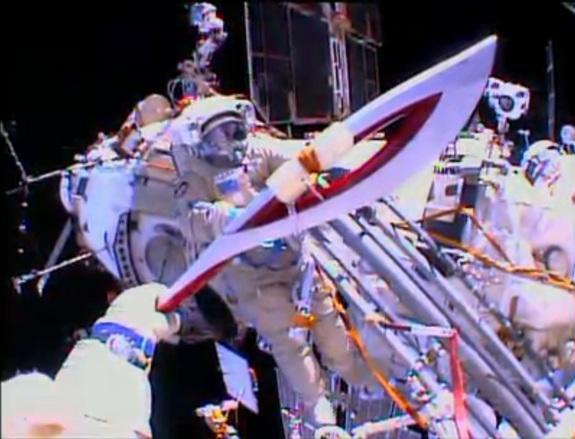 The Olympic torch is seen from the helmet camera of Russian cosmonaut Oleg Kotov in this view from a spacewalk on Nov. 9, 2013. Cosmonaut Sergey Ryazanskiy is seen awaiting the torch, which will be used in the 2014 Winter Games in Sochi, Russia