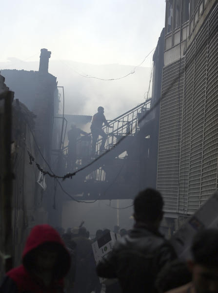 Shopkeepers save their goods at the site of a fire at an electronic appliances market in Kabul, Afghanistan, Friday, Nov. 2, 2018. Residents of the Afghan capital are grappling with the aftermath of a massive blaze that destroyed hundreds of stores at a market in Kabul.(AP Photo/Massoud Hossaini)