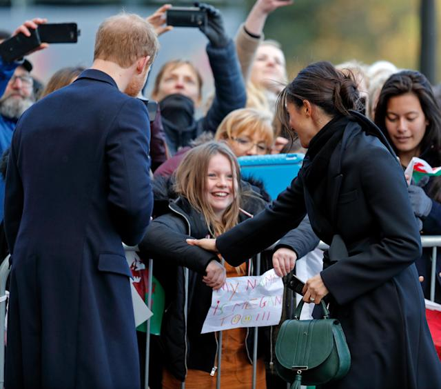 """<p>Prince Harry and Meghan Markle meet a girl holding a sign saying """"My name is Megan too"""" on a visit to Cardiff, Wales. (Photo by Max Mumby/Indigo/Getty Images) </p>"""