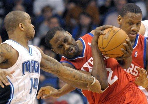 Philadelphia 76ers forward Elton Brand, center, grabs a rebound in front of Orlando Magic guard Jameer Nelson, left, and 76ers' Lavoy Allen, right, during the first half of an NBA basketball game in Orlando, Fla., Wednesday, Feb. 15, 2012. (AP Photo/Phelan M. Ebenhack)