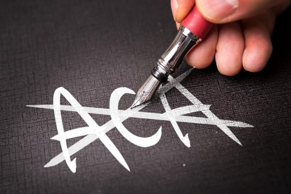 hand drawing an X over the letters ACA