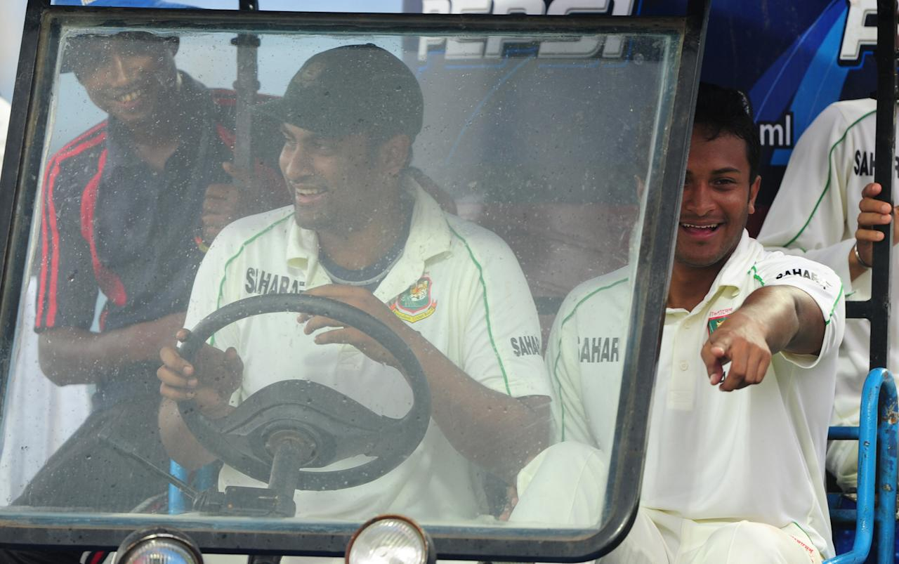 Bangladesh cricketers Tamim Iqbal (C) and Shakib Al Hasan (R) drive off the field during rain on the fourth day of the first cricket Test match between Bangladesh and New Zealand at the Zahur Ahmed Chowdhury Stadium in Chittagong on October 12, 2013. AFP PHOTO/ Munir uz ZAMAN        (Photo credit should read MUNIR UZ ZAMAN/AFP/Getty Images)