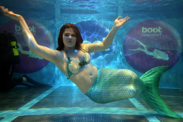 A woman dressed as a mermaid dives in a show pool at the Duesseldorf fairground during the Boot fair International Boat Show on January 23, 2013. The event, running from January 19 to January 27, features all boats, yachts, superyachts, electronics, engines and thousands of accessories from every major marine manufacturer and builder worldwide. AFP PHOTO / PATRIK STOLLARZ
