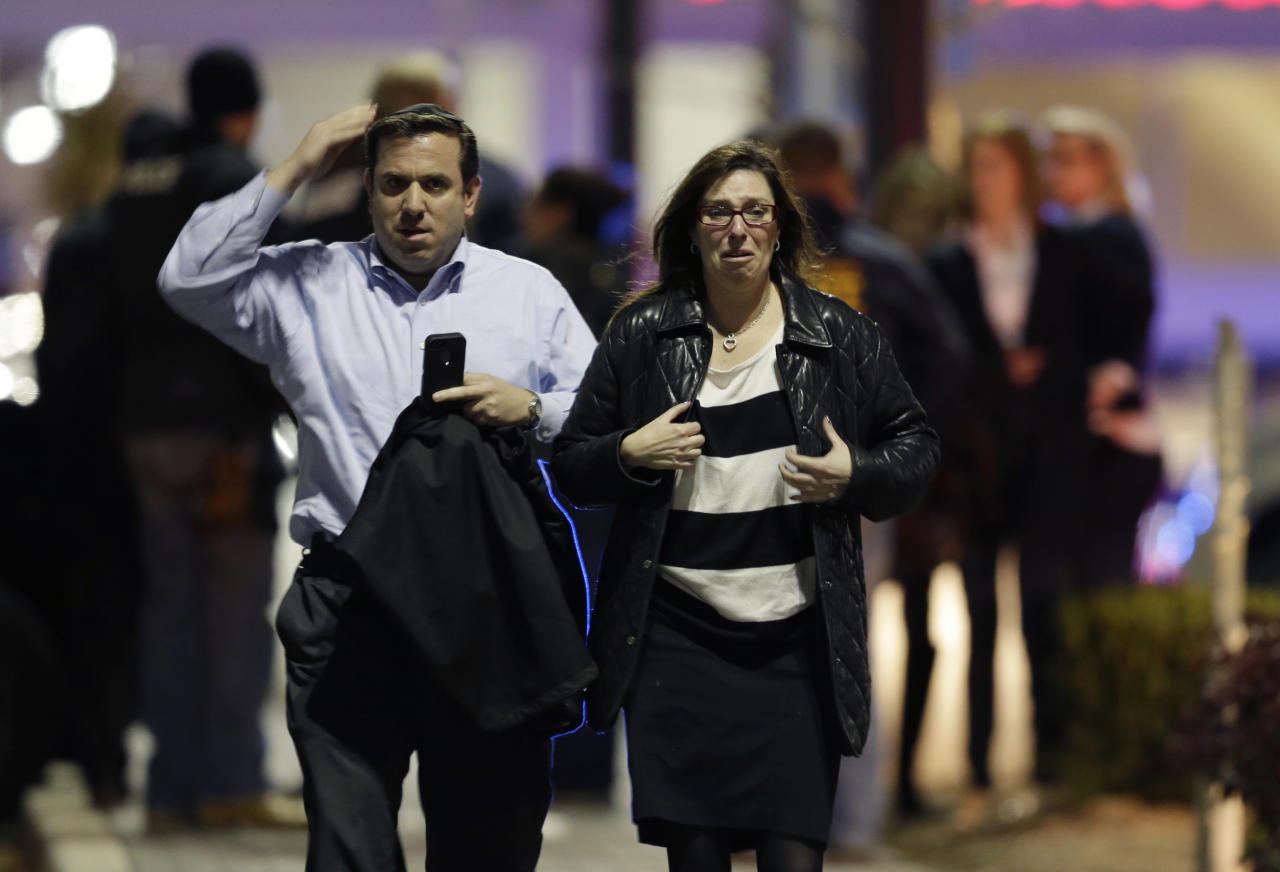 A man and woman leave the Garden State Plaza Mall with officials standing guard behind them following reports of a shooter, Monday, Nov. 4, 2013, in Paramus, N.J. Hundreds of law enforcement officers converged on the mall Monday night after witnesses said multiple shots were fired there. (AP Photo/Julio Cortez)