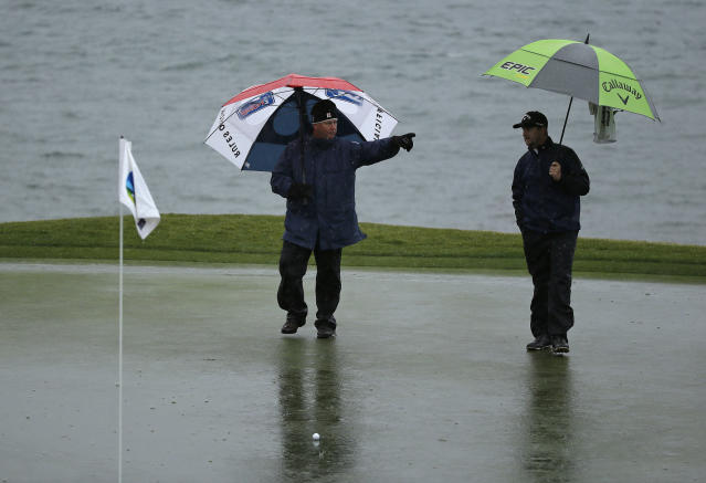 A rules official calls for greenskeepers after the ball of Brice Garnett, right, landed in standing water on the 18th green of the Pebble Beach Golf Links during the second round of the AT&T Pebble Beach Pro-Am golf tournament Friday, Feb. 8, 2019, in Pebble Beach, Calif. (AP Photo/Eric Risberg)