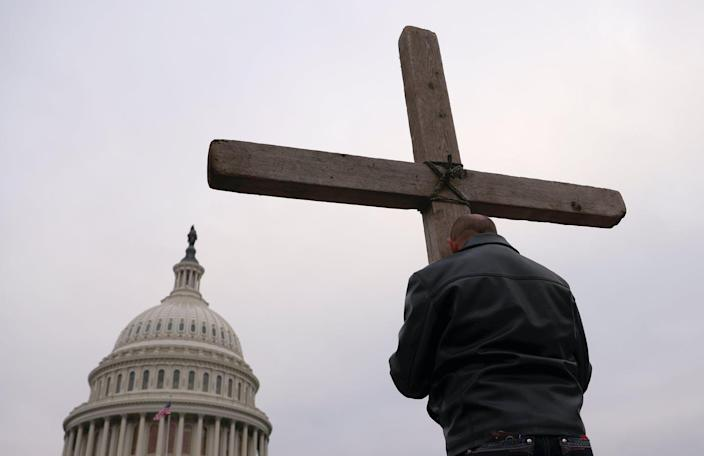 """<span class=""""caption"""">Supporters of President Trump put up a Cross outside the U.S. Capitol on Jan. 6,</span> <span class=""""attribution""""><a class=""""link rapid-noclick-resp"""" href=""""https://www.gettyimages.com/detail/news-photo/supporters-of-u-s-president-donald-trump-pray-outside-the-u-news-photo/1294872343?adppopup=true"""" rel=""""nofollow noopener"""" target=""""_blank"""" data-ylk=""""slk:Win McNamee/Getty Images"""">Win McNamee/Getty Images</a></span>"""