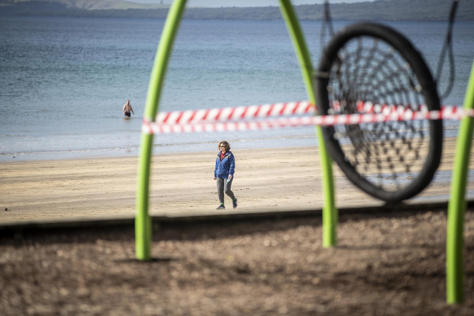 A woman walks past a closed off playground in Auckland, New Zealand Thursday, Aug. 19, 2021. Japan, Australia and New Zealand all got through the first year of the coronavirus pandemic in relatively good shape, but now are taking diverging paths in dealing with new outbreaks of the fast-spreading delta variant. (Michael Craig/New Zealand Herald via AP)