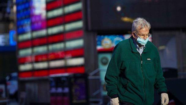 PHOTO: A man wears a face mask while walking in Times Square in New York, Nov. 18, 2020. (Wang Ying/Xinhua via Newscom)