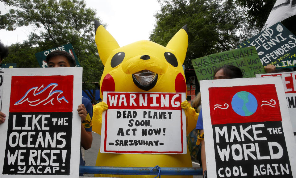 """An environmental activist, wearing a """"Pikachu"""" costume, displays a placard along with other activists during a rally to coincide with the global protests on climate change Friday, Sept. 20, 2019, at the University of Philippines campus in suburban Quezon city northeast of Manila, Philippines.  (Photo: Bullit Marquez/AP)"""