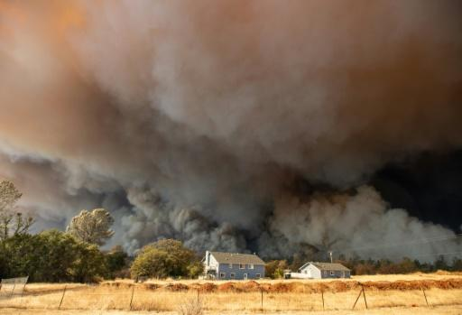 In this photo taken on November 8, 2018 a home is overshadowed by towering smoke plumes as the Camp fire races through town in Paradise, California