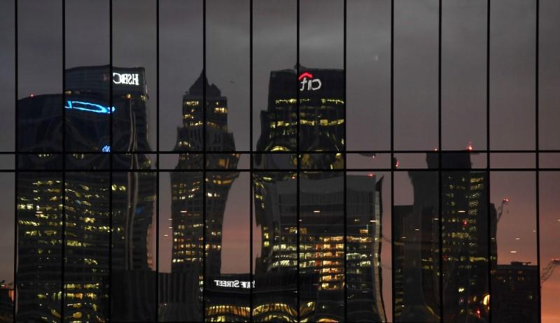 The Canary Wharf business district is seen reflected in windows at dusk in London