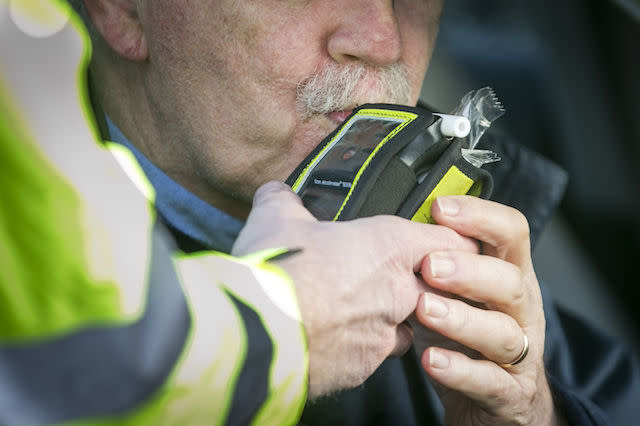A driver blows into a PSNI Road Policing officers' breathalyser during a random drink driving checkpoint in Belfast.