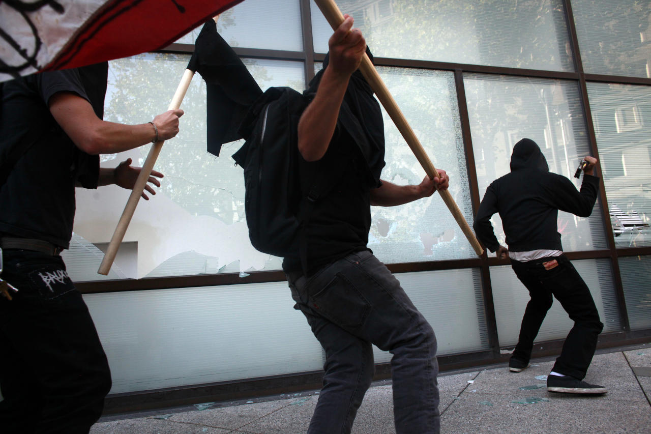 OAKLAND, CA - NOVEMBER 2:  Anarchists smash the windows of a bank during an Occupy demonstration November 2, 2011 in Oakland, California. The group called for a general strike Wednesday, and planned to march on the city's port later in the day.(Photo by Eric Thayer/Getty Images)