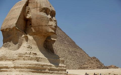 Tourists ride horses past the Great Sphinx at the historical site of the Giza Pyramids, near Cairo, Egypt - Credit:  Jon Gambrell