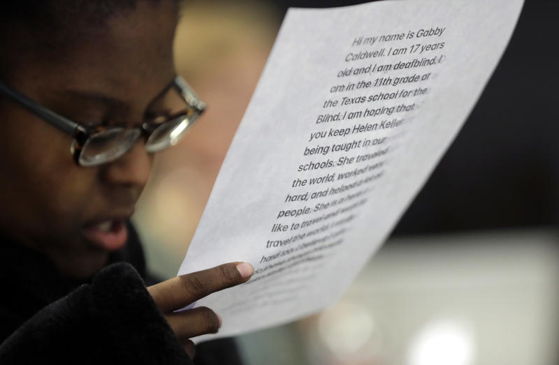 Gabrielle Caldwell, who is partially deaf and blind, looks over her notes where she testified before the Texas School Board during public testimony as they prepares to vote on history curriculum, Tuesday, Nov. 13, 2018, in Austin, Texas. The Republican-controlled board is hearing from activists and academics who are defending or decrying proposed edits meant to streamline academic standards for history. (AP Photo/Eric Gay)