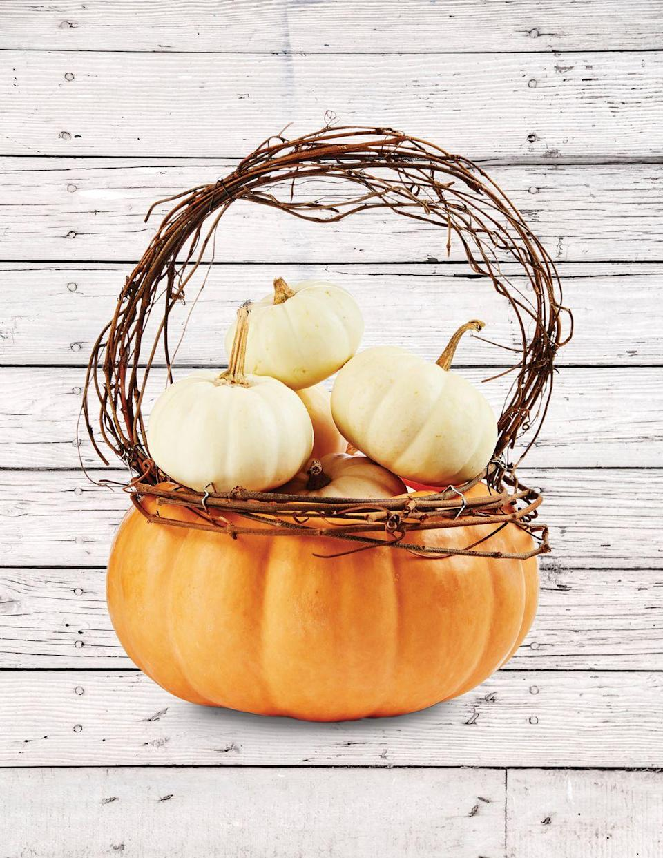 <p>Pumpkins inside pumpkins? It's fall inception, and we're loving every bit of it.</p><p><strong>Make the basket:</strong> Cut off the top quarter of a flat pumpkin (this is a Musquee de Provence variety); scoop out pulp and seeds. Attach lengths of grapevine just below the opening with T-pins. Attach a grapevine handle just inside the opening with T-pins. Nestle mini pumpkins in the basket. </p>