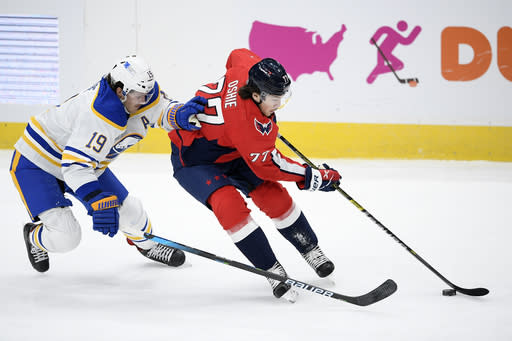 Washington Capitals right wing T.J. Oshie (77) skates with the puck next to Buffalo Sabres defenseman Jake McCabe (19) during the first period of an NHL hockey game, Sunday, Jan. 24, 2021, in Washington. (AP Photo/Nick Wass)