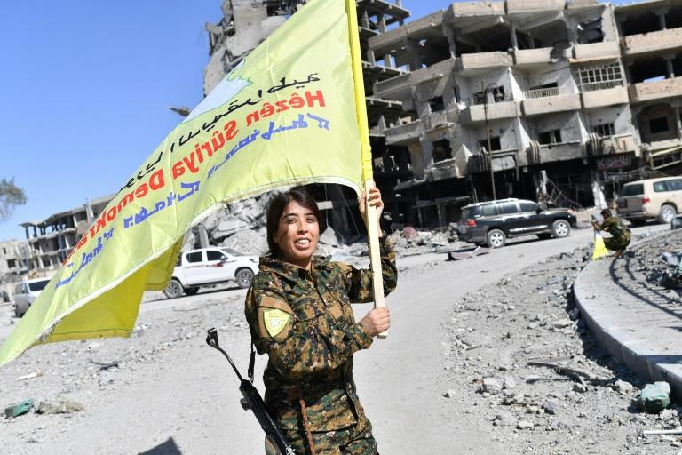 Rojda Felat, a Syrian Democratic Forces (SDF) commander, waves her group's flag at the iconic Al-Naim square in Raqa on October 17, 2017