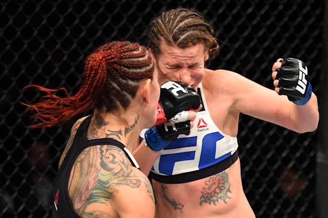 Cris Cyborg punches Leslie Smith in their women's catchweight bout during UFC 198. (Getty)