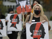 Women's rights activists with posters of the Women's Strike action protest against recent tightening of Poland's restrictive abortion law in front of the parliament building as inside, guards had to be used to shield right-wing ruling party leader Jaroslaw Kaczynski from angry opposition lawmakers, in Warsaw, Poland, on Tuesday, Oct. 27, 2020. Massive nationwide protests have been held ever since a top court ruled Thursday that abortions due to fetal congenital defects are unconstitutional. Slogan reads 'Women's Strike'. (AP Photo/Czarek Sokolowski)