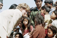 """FILE - In this file photo dated Friday, March 5, 1993, Britain's Diana talks with Nepalese children in the village of Panauti, in the foothills of the Himalayas, as some thousands of villagers, mostly children, turned out to greet her. For someone who began her life in the spotlight as """"Shy Di,"""" Princess Diana became an unlikely, revolutionary during her years in the House of Windsor. She helped modernize the monarchy by making it more personal, changing the way the royal family related to people. By interacting more intimately with the public -- kneeling to the level of children, sitting on edge of a patient's hospital bed, writing personal notes to her fans -- she set an example that has been followed by other royals as the monarchy worked to become more human and remain relevant in the 21st century. (AP Photo/Barbara Walton, File)"""