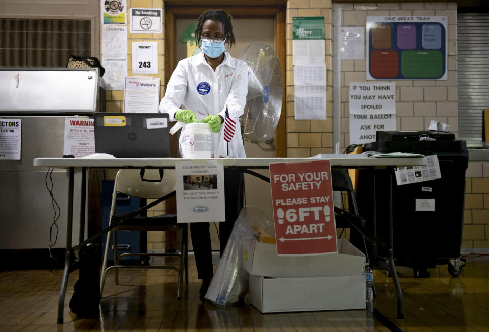 Debra Moore sanitizes her workspace during primary Election Day on Aug. 4, 2020, in Detroit. (Nicole Hester / Mlive.com via AP file)