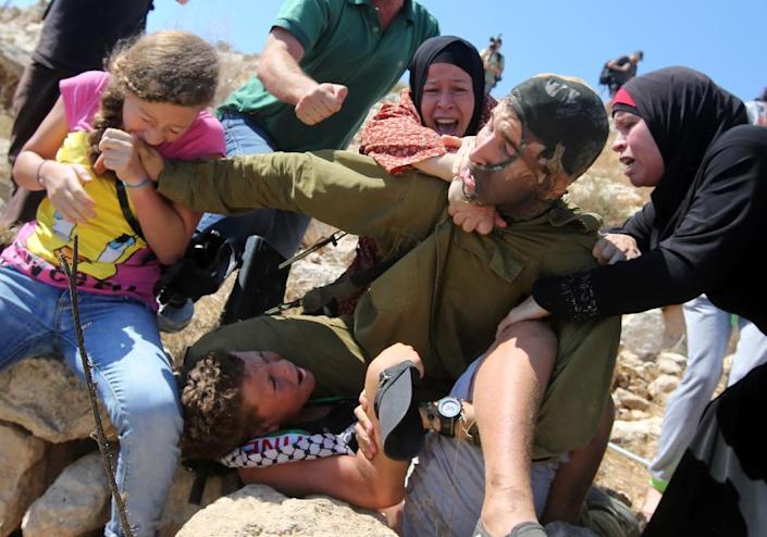 A Palestinian girl and women figth to free a Palestinian boy (bottom) held by an Israeli soldier (C) during clashes between Israeli security forces and Palestinian protesters following a march against Palestinian land confiscation last year (AFP Photo/Abbas Momani)