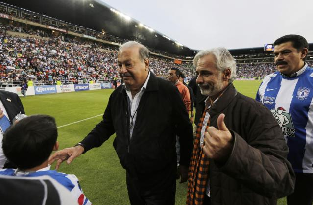 Owner of the Leon soccer team and billionaire Carlos Slim (L) arrives with owner of the Pachuca soccer team Jesus Martinez (2nd R) before their Mexican league championship final soccer match between Pachuca and Leon at the Hidalgo stadium in Pachuca May 18, 2014. REUTERS/Henry Romero (MEXICO - Tags: SPORT SOCCER BUSINESS)