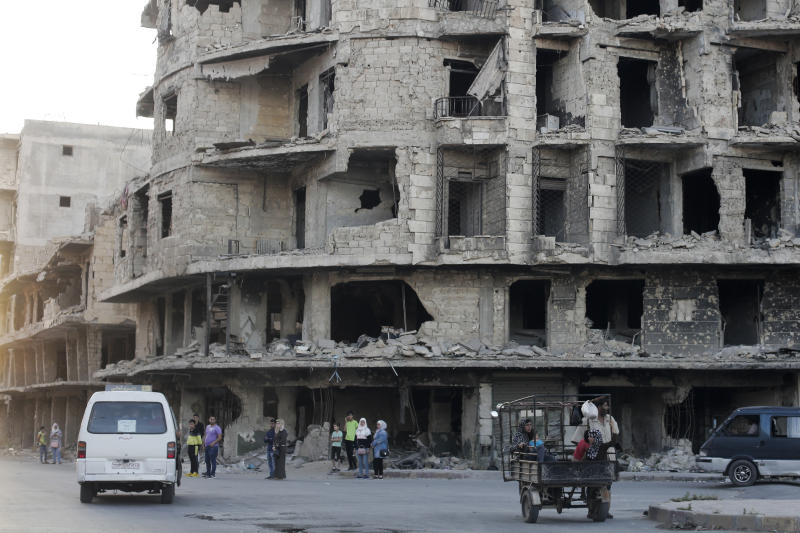 In this Friday, July 26, 2019 photo, Syrians wait for a public transportation in Aleppo, Syria. Rebels still frequently strike with shelling and mortars into Aleppo, killing civilians nearly three years after the government recaptured the city. Aleppo is a symbol of how President Bashar Assad succeeded in turning the tide in Syria's long civil war with a series of wins, but it's equally a symbol of how he's been unable to secure a final victory. Half of Aleppo remains in ruins, and rebels remain on the doorstep. (AP Photo/Hassan Ammar)
