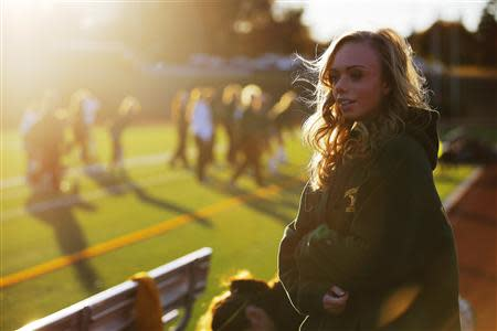 Seventeen year-old Hannah Steenhuysen watches her high school's girls soccer team prepare for a game against Bishop Feehan in Attleboro, Massachusetts October 25, 2013. REUTERS/Brian Snyder