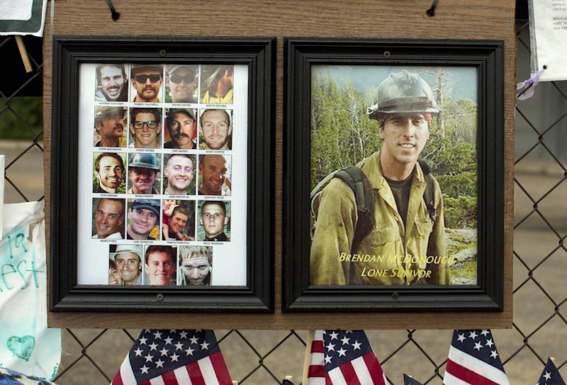 FILE - In this July 5, 2013 file photo, photos of the 19 fallen Granite Mountain Hotshot firefighters and the lone survivor of the fatal blaze hang on the fence outside Fire Station No. 7 in Prescott, Ariz. The wildfire outside the small town of Yarnell, Ariz. that began with a lightning strike and caused little immediate concern because of its remote location and small size quickly blazed into an inferno, leading officials to rapidly order more resources in the hours before flames killed 19 members of an elite Hotshot crew, according to a report released Monday, July 15, 2013. (AP Photo/Julie Jacobson, File)