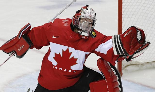 Goalkeeper Shannon Szabados of Canada (1) is hit in the face shield by the puck during the third period of the women's gold medal ice hockey game against the United States at the 2014 Winter Olympics, Thursday, Feb. 20, 2014, in Sochi, Russia. (AP Photo/Petr David Josek)